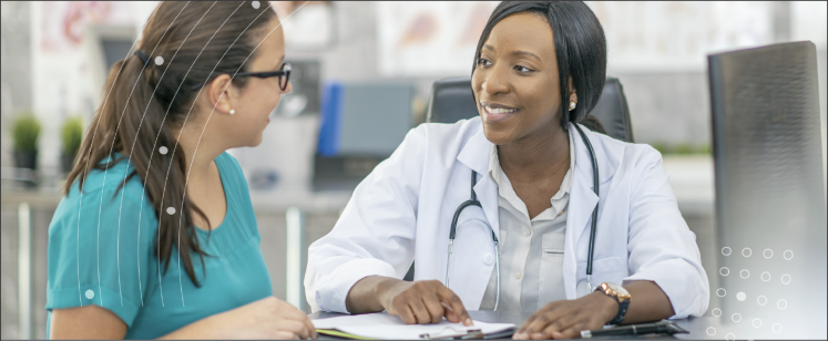 Female doctor speaking to woman pointing at a piece of paper